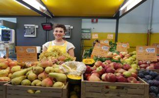 Giovane agricoltrice che vende prodotti tipici della Dieta Mediterranea